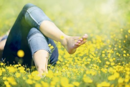 Person liegt entspannt auf einer Blumenwiese